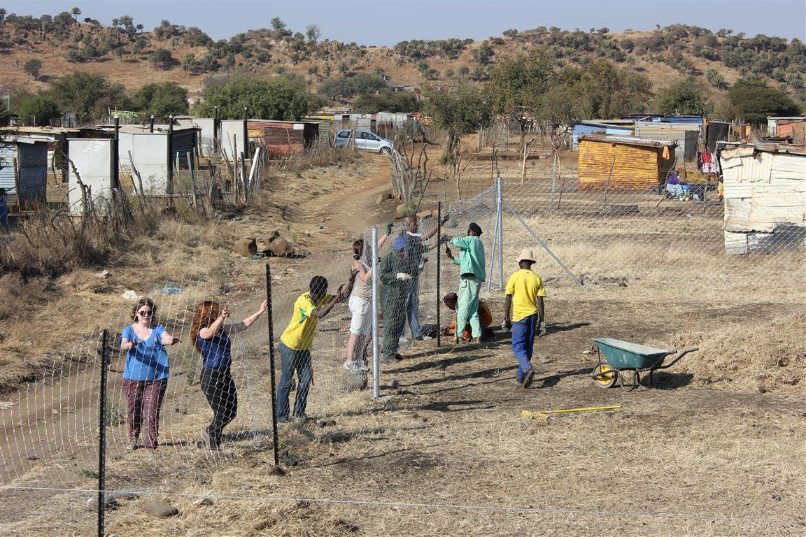 Volunteers putting up fencing in Nkaneng at site for new creche  (South Africa)